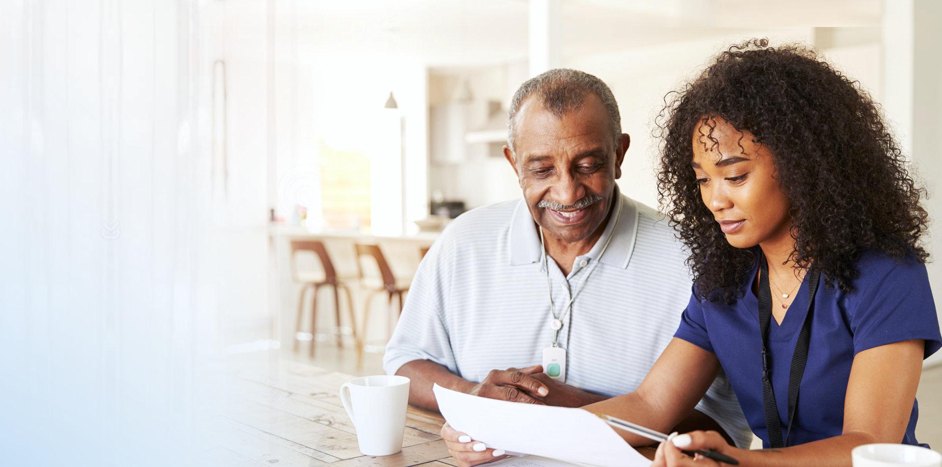 caregiver and senior man reading